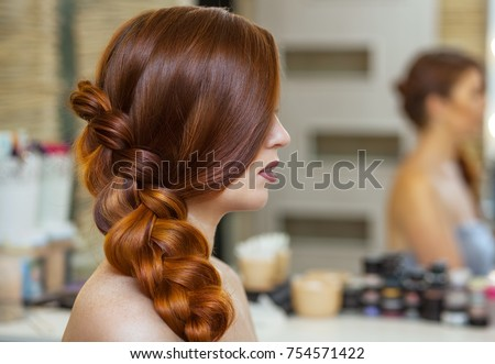 Beautiful girl, with long, red-haired hairy. hairdresser weaves a French braid, close-up in a beauty salon. Professional hair care and creating hairstyles.