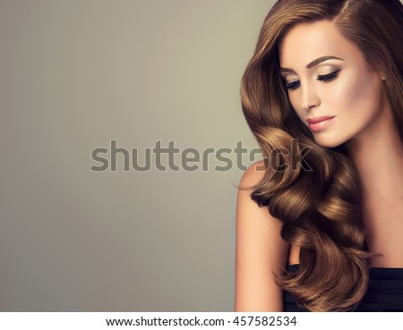 Stock Photo Beautiful girl with long wavy  and shiny  hair . Brunette woman  with curly hairstyle