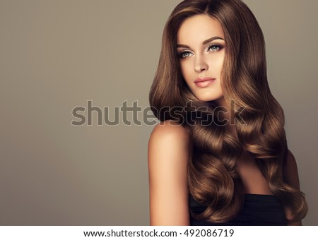Beautiful girl with long wavy  and shiny  hair . Brunette woman  with curly hairstyle  #492086719