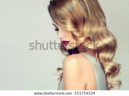 Beautiful girl with long wavy hair .  Blonde with curly hairstyle and red lips #511754524