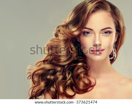 Beautiful girl with long wavy hair .  Brunette  model with curly hairstyle