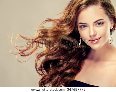 Shutterstock Beautiful girl with long wavy hair .  Brunette with curly hairstyle