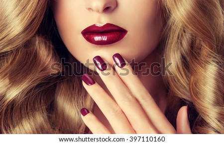 Beautiful girl with long wavy hair .  woman with red manicure .  girl with plum color nail Polish on the nails . Makeup and cosmetics