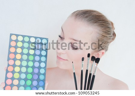 beautiful girl with makeup brushes and make-up eye shadows