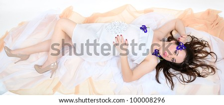 beautiful girl with makeup in a white cloth lies on fabrics