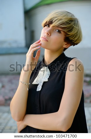 Beautiful girl with modern haircut standing in the street