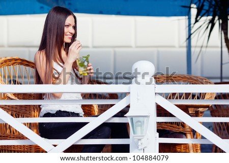 Beautiful girl with mojito drink in cafe