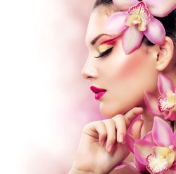 Beautiful Girl With Orchid Flowers.Beauty Model Woman Face. Perfect Skin. Professional Make-up.Makeup.Isolated on a White Background. Fashion Art