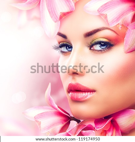 Beautiful Girl With Orchid Flowers.Beauty Model Woman Face. Perfect Skin. Professional Make-up.Makeup. Fashion Art