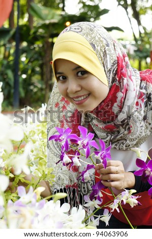 beautiful girl with orchid flowers in the garden