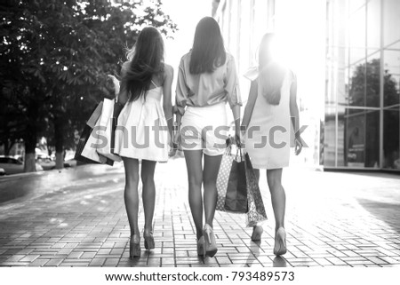 Beautiful girl with packages after shopping A picture of a group of happy friends shopping in the city. Girl walking around the city after shopping. good mood. black and white photo