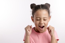 beautiful girl with raised arms is shouting beacause she has got excellent marks at school. copyspace. close up portrait. kid with closed eyes and clenched fists celebrating success. copyspace