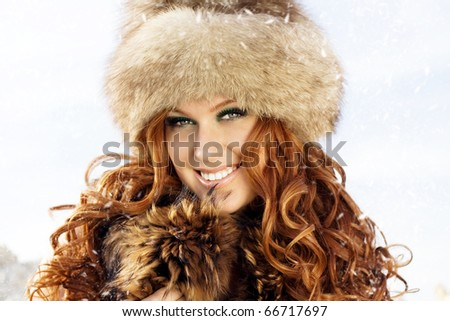 beautiful girl with red hair coat for the winter background