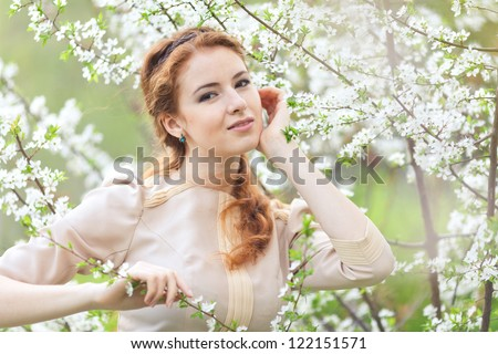 beautiful girl with red hair in spring cherry garden