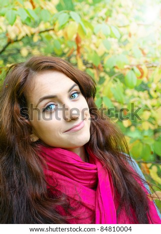 beautiful girl with red scarf and silky long hair over sunny yellow autumn leaves in the park