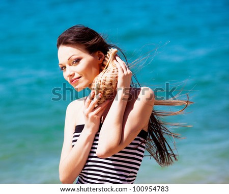 Beautiful girl with seashell in hands