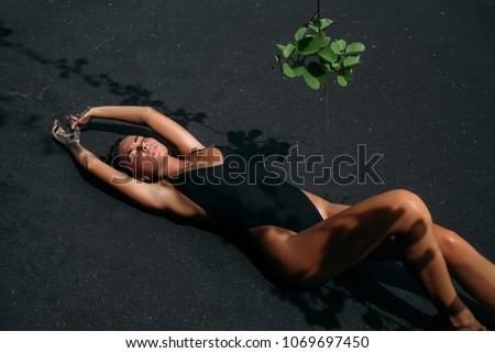 Beautiful girl with sexy body in black swimsuit lying on the beach with black volcanic sand. Young model with curly hairs, tanned skin posing and relaxing in the journey.