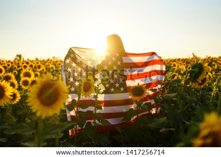 Beautiful girl with the American flag in a sunflower field. 4th of July. Fourth of July. Freedom. Sunset light The girl smiles. Beautiful sunset. Independence Day. Patriotic holiday.  #1417256714