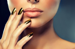 Beautiful girl with the Golden makeup and gold  metal nails.  Fashion woman Portrait