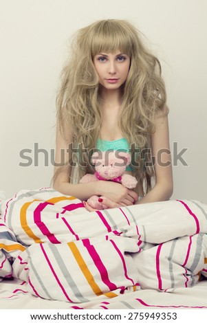 beautiful girl with toy in the bed. beauty young woman in the morning.toy bear
