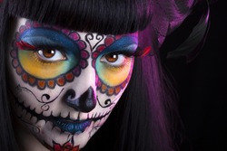Beautiful girl with traditional mexican dia delos muertos face mask
