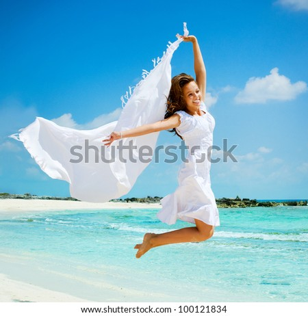 Beautiful Girl With White Scarf Jumping on The Beach. Travel and Vacation. Freedom Concept