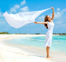 Beautiful Girl With White Scarf Jumping on The Beach. Travel and Vacation. Freedom Concept. Full length portrait