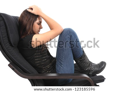 Beautiful girl worried seated on a couch with a white isolated background