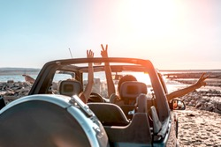 Beautiful girls and young people traveling with jeep car in a sunset in a beach landscape