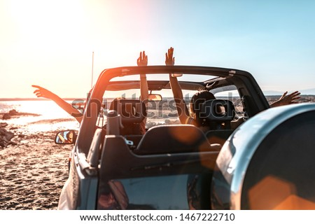 Photo of  Beautiful girls and young people traveling with jeep car in a sunset in a beach landscape