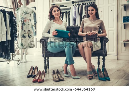 Beautiful girls are choosing high-heeled shoes, looking at camera and smiling while doing shopping in boutique #644364169