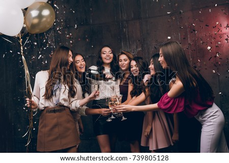 Beautiful girls celebrate New Year. Enjoying carefree time together. Group of beautiful young girl throwing gold confetti and looking happy and drinking champagne #739805128