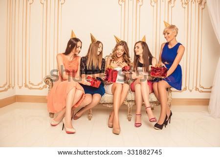 Beautiful girls celebrating birthday sitting on the sofa