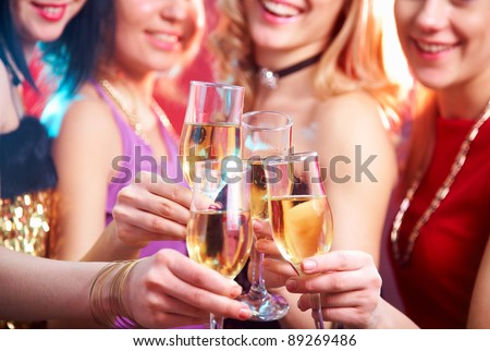 Beautiful girls clink glasses of champagne at a party