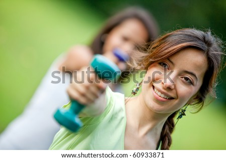 Beautiful girls exercising outdoors with free weights