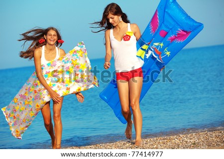 Beautiful girls having fun in water at beach - stock photo