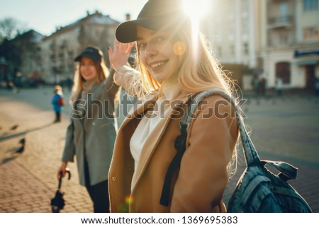 Beautiful girls in a city. Women are having a rest. Girlfriends in caps
