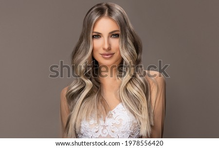 beautiful girls in  white wedding dresses  with hair coloring in ultra blond. Stylish hairstyle curls done in a beauty salon. Fashion, cosmetics and makeup.Adorable brides