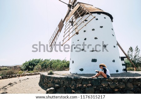 Stock Photo beautiful girls reading a book in totally freedom and alternative country side place. sitting on a stone wall with ancient traditional windmill in background.  Happiness and travel concept enjoy life