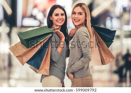 Beautiful girls with shopping bags are looking at camera and smiling while doing shopping in the mall