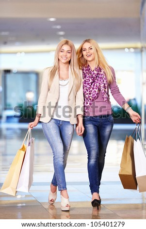 Beautiful girls with shopping bags walking in the store - stock photo