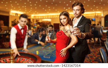 Beautiful glamour couple against the background of casino poker roulette.