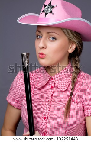 Beautiful glamour cowboy blows on the barrel