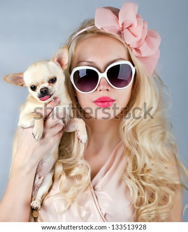 beautiful glamour woman in sunglasses with small dog in hands