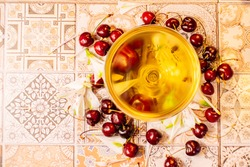 Beautiful glass of white wine with cherries and flowers on a tile background, mosaic tile table, sunlight, dinner, romance, date, light through the glass