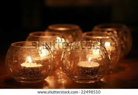 beautiful glassy candle holders with burning tea candles arranged with symmetry