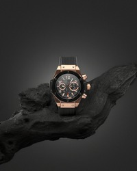 Beautiful gold men's watch with a black strap on a wooden stand, on a gray background. Beautiful gold watch. A luxury brand watch