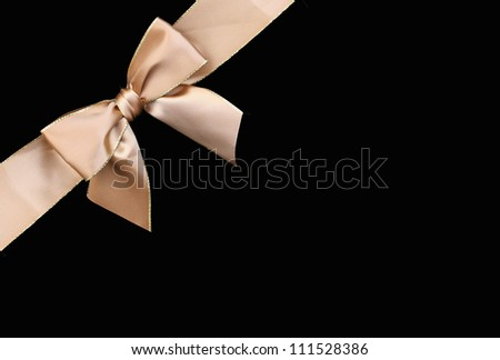 Beautiful gold ribbon gift bow with golden trim isolated on black background