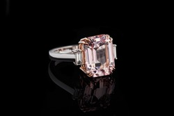 beautiful gold ring with morganite and diamond gemstones on a black background close-up
