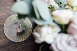 beautiful gold wedding rings on wood floor next to bouquet and shoes